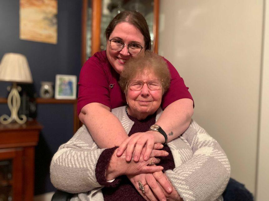 Judi Bemmer stands behind her mother, Gill Bemmer, hugging her from behind