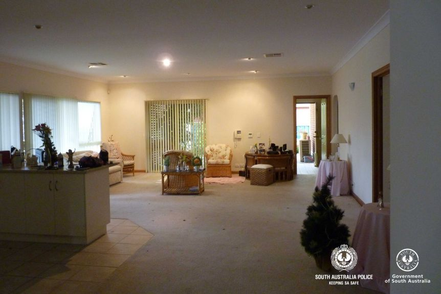 The inside of a home. Three wicker chairs can be seen and a cream coloured couch. There is also a christmas tree.