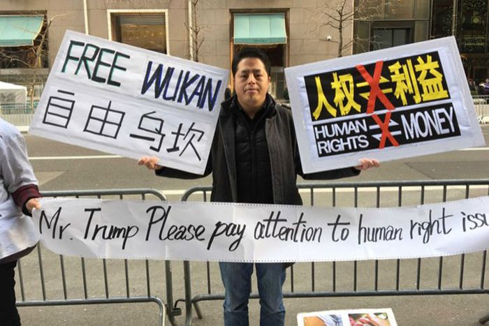 """A man holds up signs on the road """"Free Wukan"""" and """"Trump please pay attention to human right issues"""""""